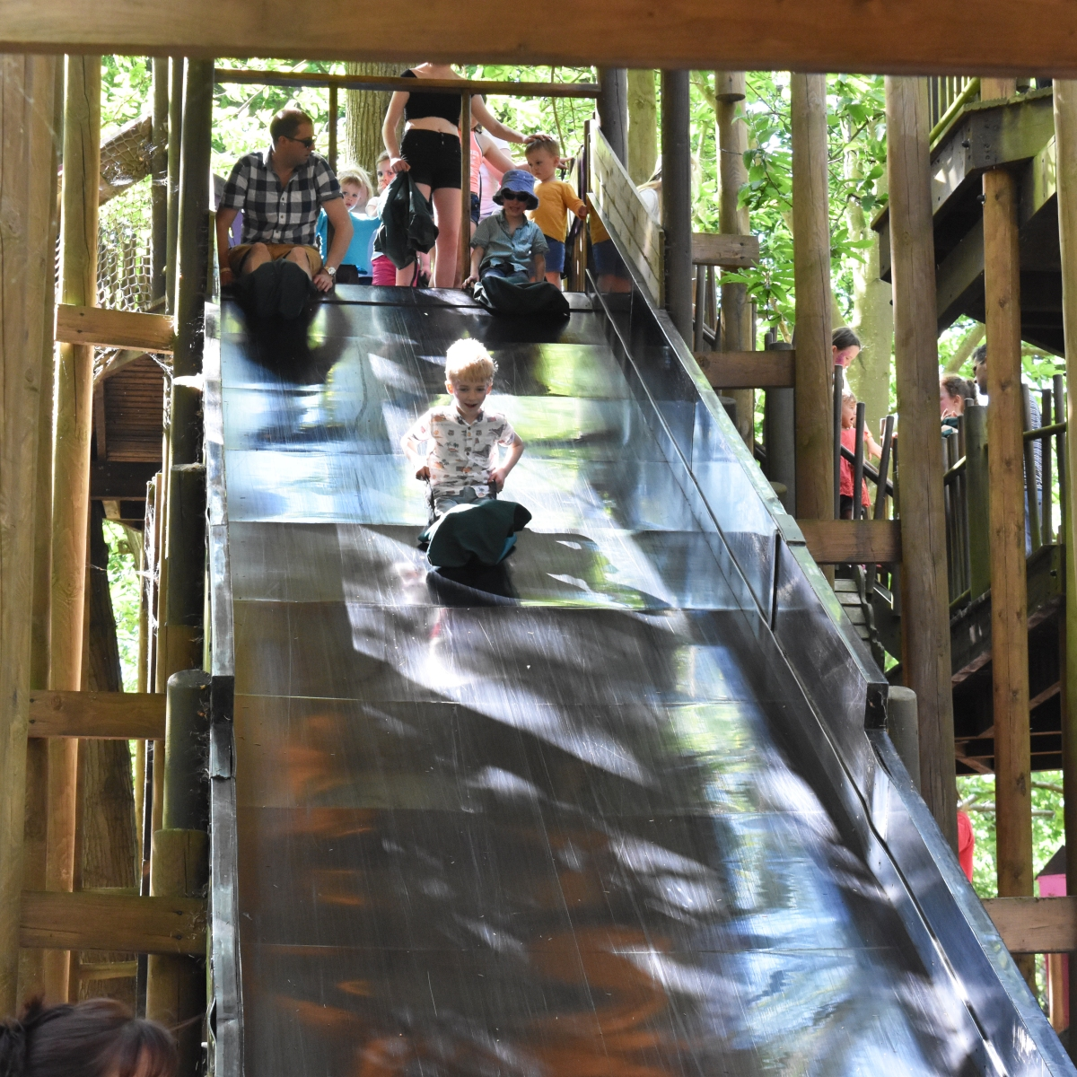 A photograph of Rob, Ollie and Ben at the top of the slippery slope slide.