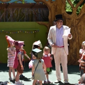 A photograph of Tom Blofeld reading to children on the storytelling stage.