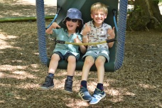A photograph of Ben and Ollie in a large chair swing.