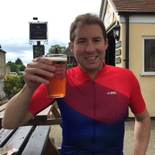A photograph of Rob with a pint of London Pride sitting on a picnic-style bench outside the Village Inn in Witchford.