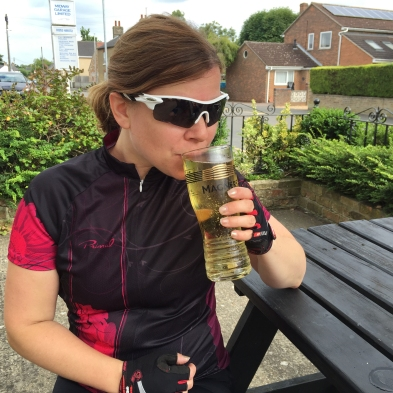 A photograph of Emma with a pint of cider sitting on a picnic-style bench outside the Village Inn in Witchford.
