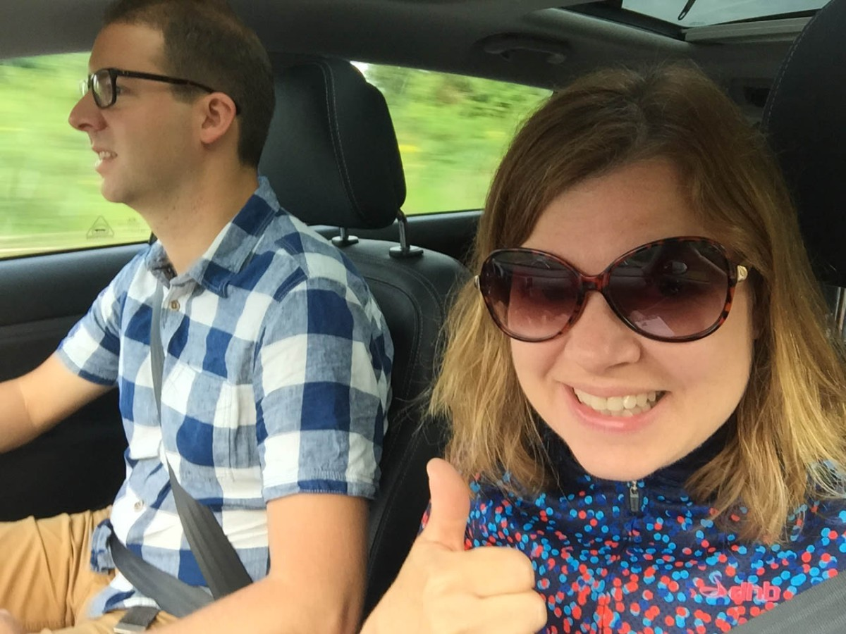 A photograph of Emma in the car giving a thumbs up. Rob is driving to Bury.