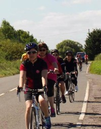 A photograph of Emma at the front of a group of riders on the Pink Ribbon Ride.