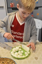 A photograph of Ollie cutting up the lard into small squares.