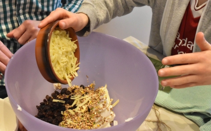 A photograph of a bowl of grated cheese being poured into a bowl with the seed, lard and raisins.