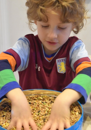A photograph of Ben playing with the bird seed.