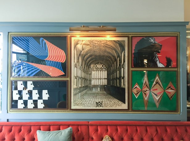 A photograph showing five colourful modern prints surrounding a black and white image inside a Cambridge college chapel