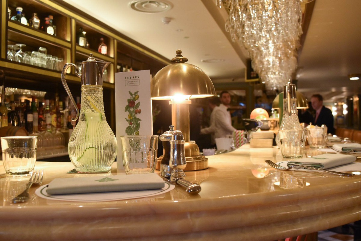 A photograph showing a close up of the table setting on the bar, each with its own lamp
