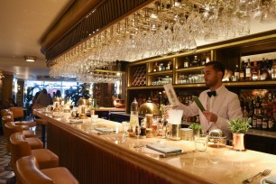 A photograph looking down the bar with a barman behind in white jacket and black bowtie