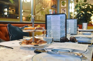 A photograph of Emma's table with menu standing up behind small stacked trays holding pastries and jams