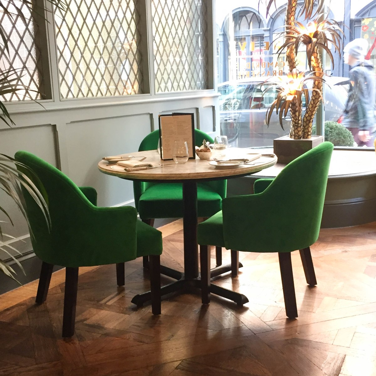 A photograph of three chairs of classic Ivy green around a table close to the window