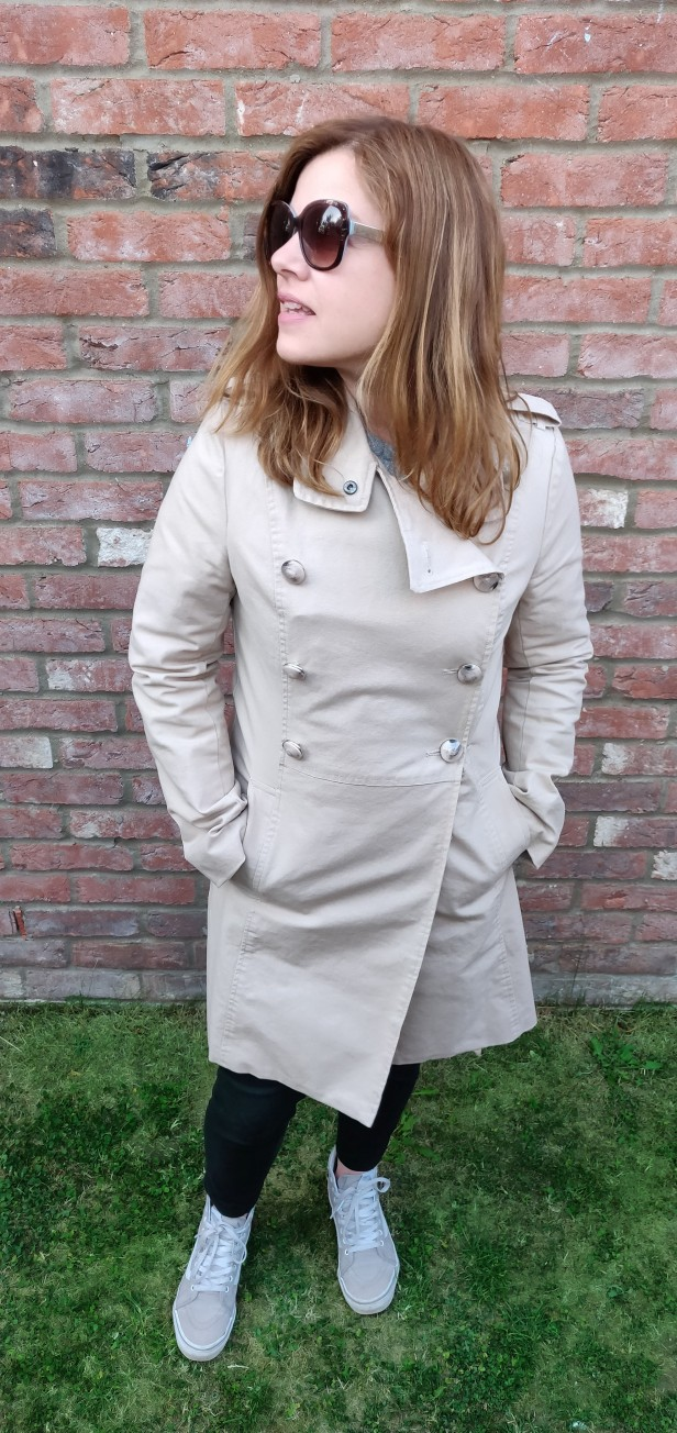 A photograph of Emma standing in her garden, trying to model the new trench coat.