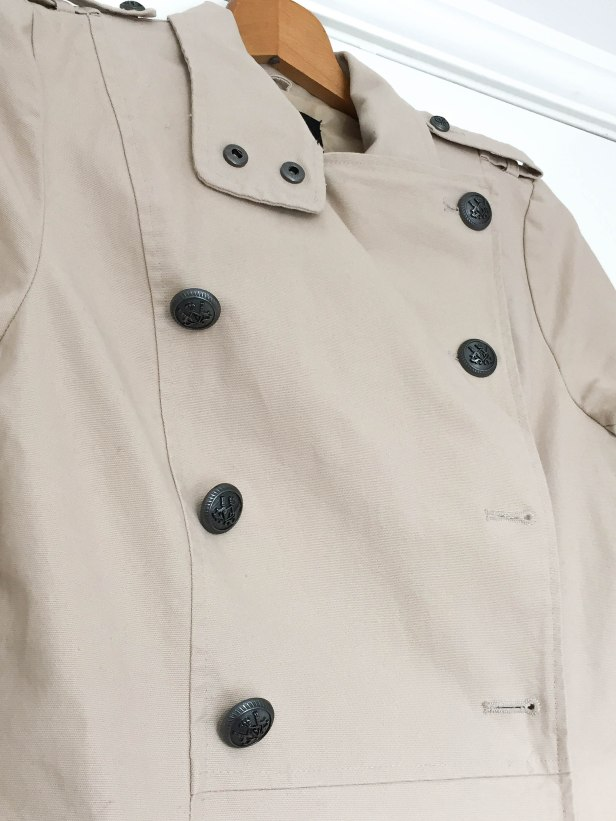 A close-up photograph of Emma's coat before the old buttons were replaced