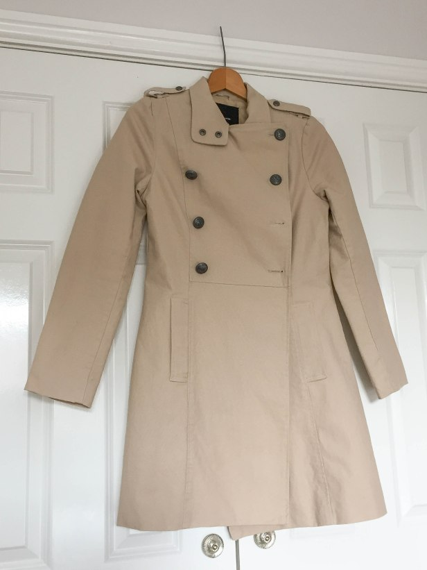 A photograph of Emma's coat hanging up with the old buttons, a few of them missing.