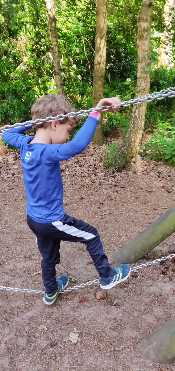 A photograph of Ben going along a chain bridge in the park obstacle course.