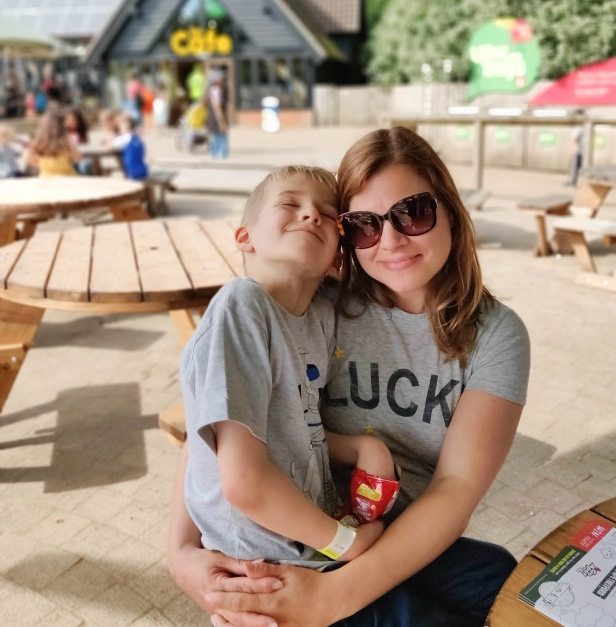 A photograph of Ollie sitting on Emma's lap in the eating area with snacks.