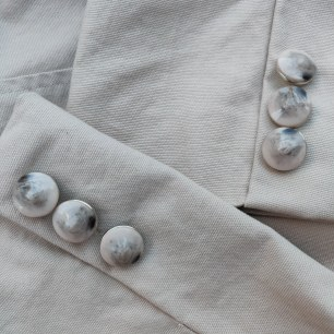 A close-up photograph of the cuffs of both sleeves showing the new buttons