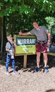 "A photograph of Ollie and Rob at the end, next to a sign saying ""Hurrah! You did it!"""