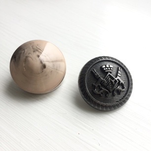 A photograph of a new and old button for comparison