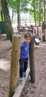 A photograph of Ben going along a log bridge in the park obstacle course.