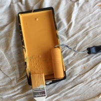 A photo of a paint tray full of amber paint, a paintbrush and roller