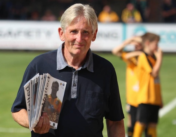 A photo of Dave Matthew-Jones carrying programmes at a recent pre-season match