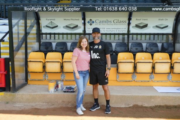 A photo of Emma standing with Joe Dunne in front of the updated home dugout