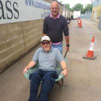 A photo of Ian Darler pushing Mick Radford in a wheelbarrow