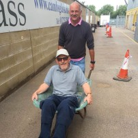 A photo of Ian Darler pushing Mick Radford in a wheelbarrow
