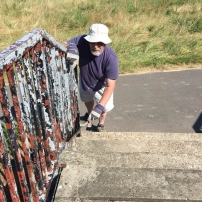 A photo of Les Weston repainting one of the bridges that cross from Coldham's Common to the Habbin Stand