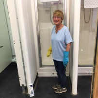 A photo of Wendy Twinn in the training ground shower room making the tiles sparkle