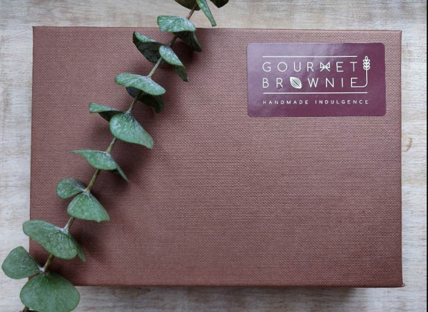 A photograph of the Gourmet Brownie gift box with a sprig of eucalyptus across the top.