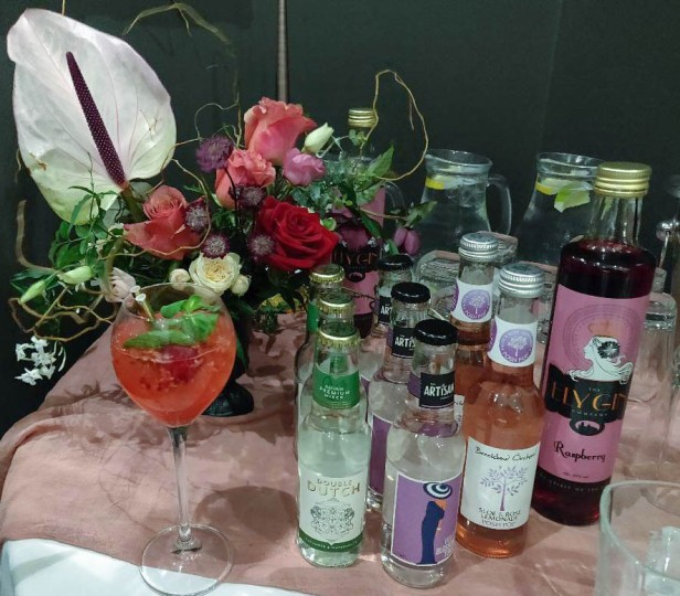 A photograph of the Ely Gin table with Raspberry Gin and a selection of mixers and a bouquet from Farm Flowers.