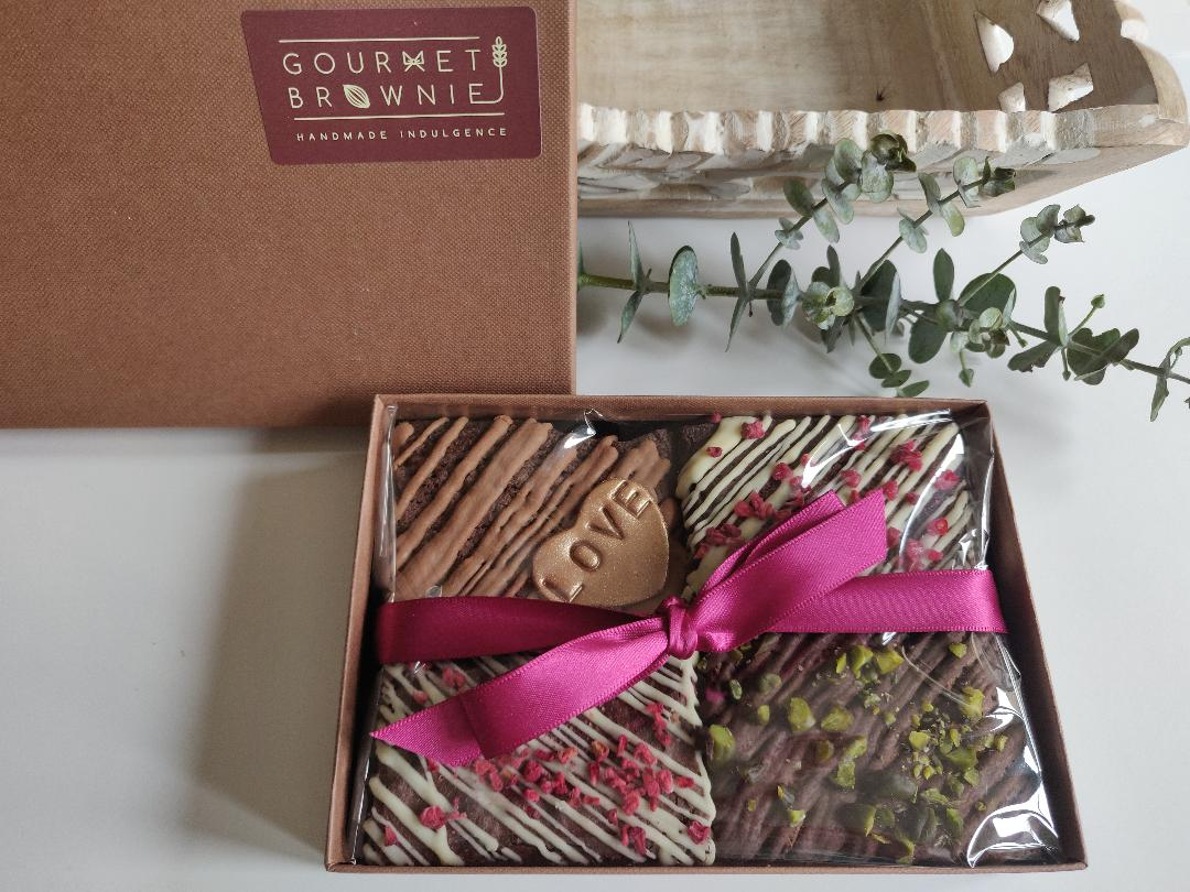 A photograph of four brownies inside the gift box with a ribbon around.