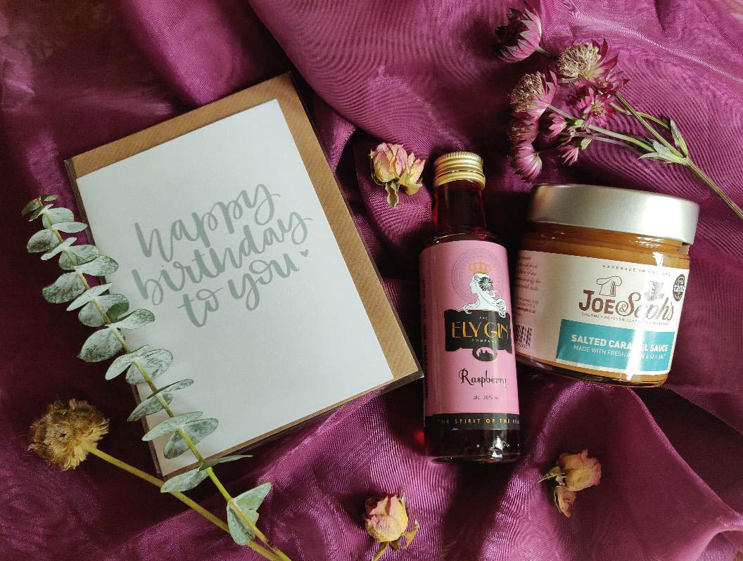 A photograph of a birthday card, bottle of raspberry gin, jar of salted caramel and eucalyptus from the bouquet sitting on a magenta scarf.