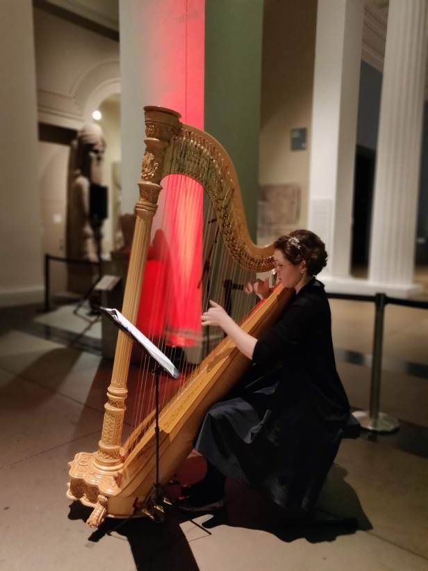 A harpist playing some Christmas tunes on the harp in Gallery 4