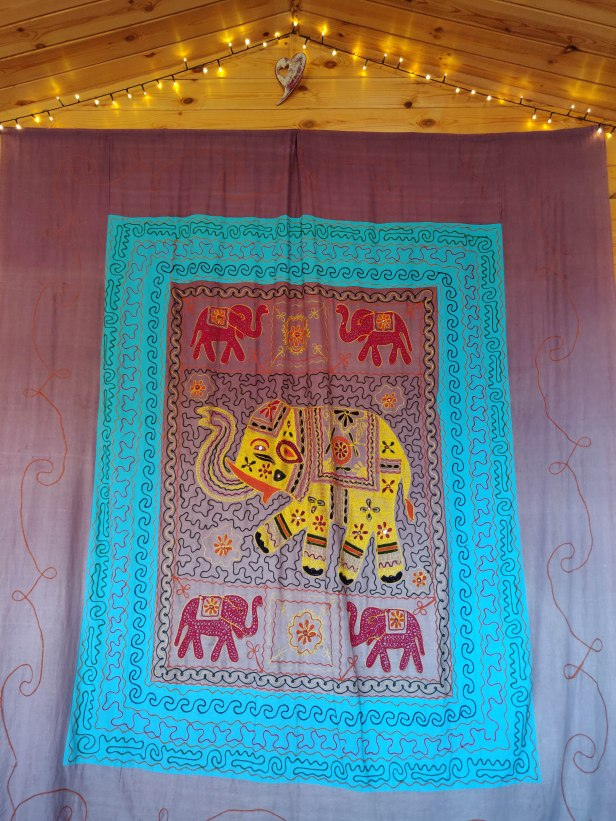 A colourful blanket hangs on the wall depicting a large yellow Indian elephant in the centre