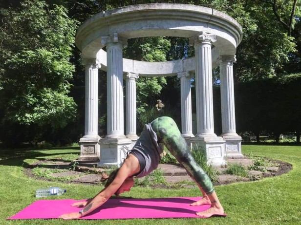 Sally demonstrating a Downward Dog pose to her class. She has a pink mat and is in front of a Greek-style stone pergola in a garden, surrounded by lawn.