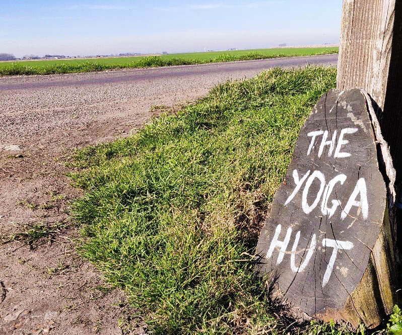 Log slice with The Yoga Hut painted in white. Fenland views across nearby fields.