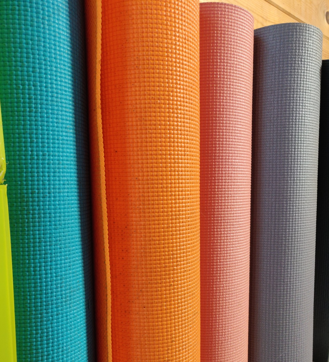 Rolled up yoga mats of all colours standing in a row