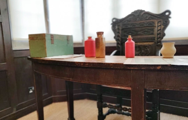 Wooden desk with a box and bottles on top